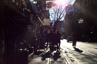 Backlit pedestrians and strong flare present. New York City, New York.