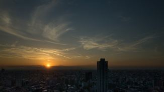 The sun is setting just to the  left of Mt. Fuji.
