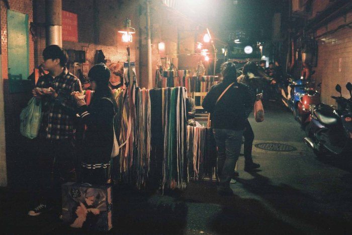Very poorly lit scene of a shoelace and repair vendor  (Canon Canonet QL17 with Fujifilm X-TRA 400)